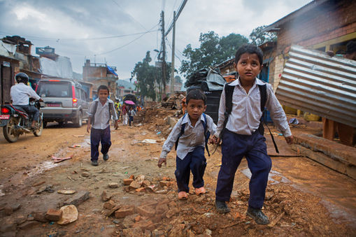 CHILDREN ESCAPING FROM THE RAIN AMONG THE RUBBLE Chauthara, Sindhupalchowk District