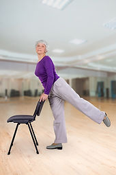 Happy charming beautiful elderly woman is doing exercise on a chair. Exercising gymnastics