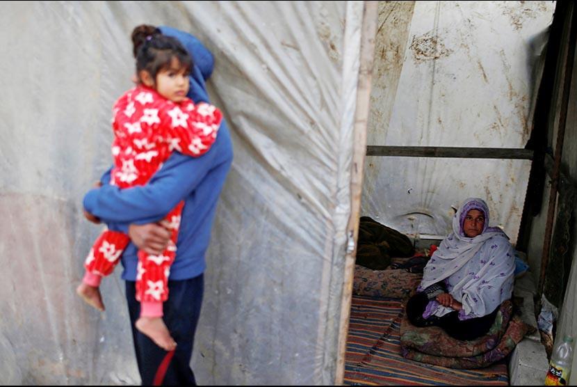 Wanita Palestina berdiam di dalam tenda plastik dekat rumahnya yang hancur di selatan Jalur Gaza, Senin (13/1). Memasuki musim dingin warga Palestina harus berjuang melawan hawa dingin yang akan mecapai puncaknya pada bulan ini. (FOTO : Mohamed Salem/Reuters)