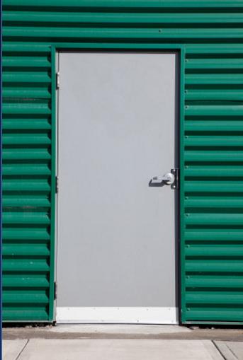 a grey door next to green walls