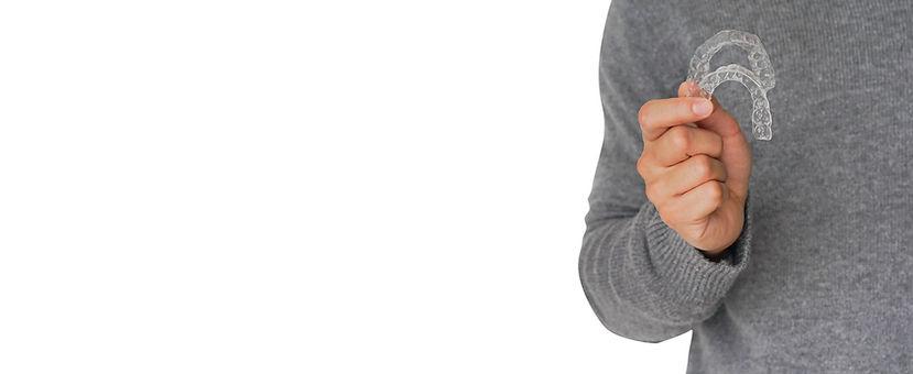Hombre con jersey gris sujetando dos ferulas de ortodoncia invisible