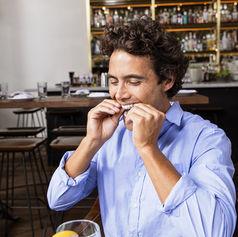 Hombre joven en restaurante quitandose aparato Invisalign para comer