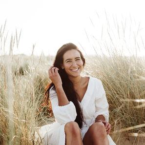 Paciente de GM Ortodoncia sonriendo en duna