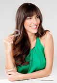 Chica joven sonriente con top verde sujetando ortodoncia invisible