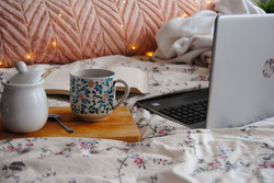 Coffee set up and computer on bed