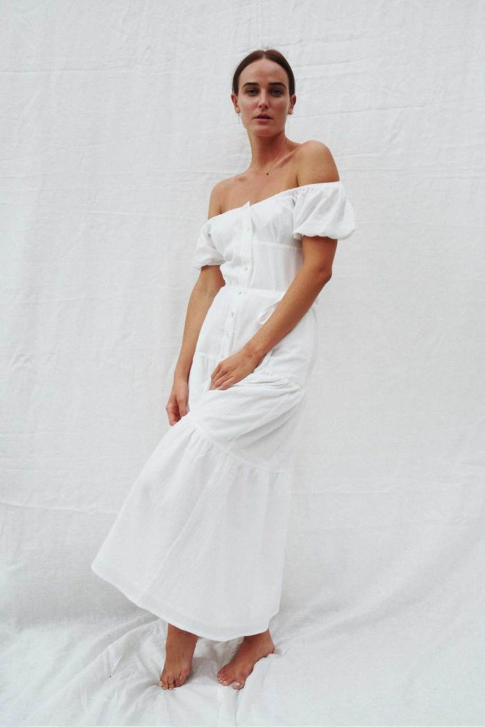 Bride wearing off-the-shoulder, relaxed cotton midi dress with bare feet.
