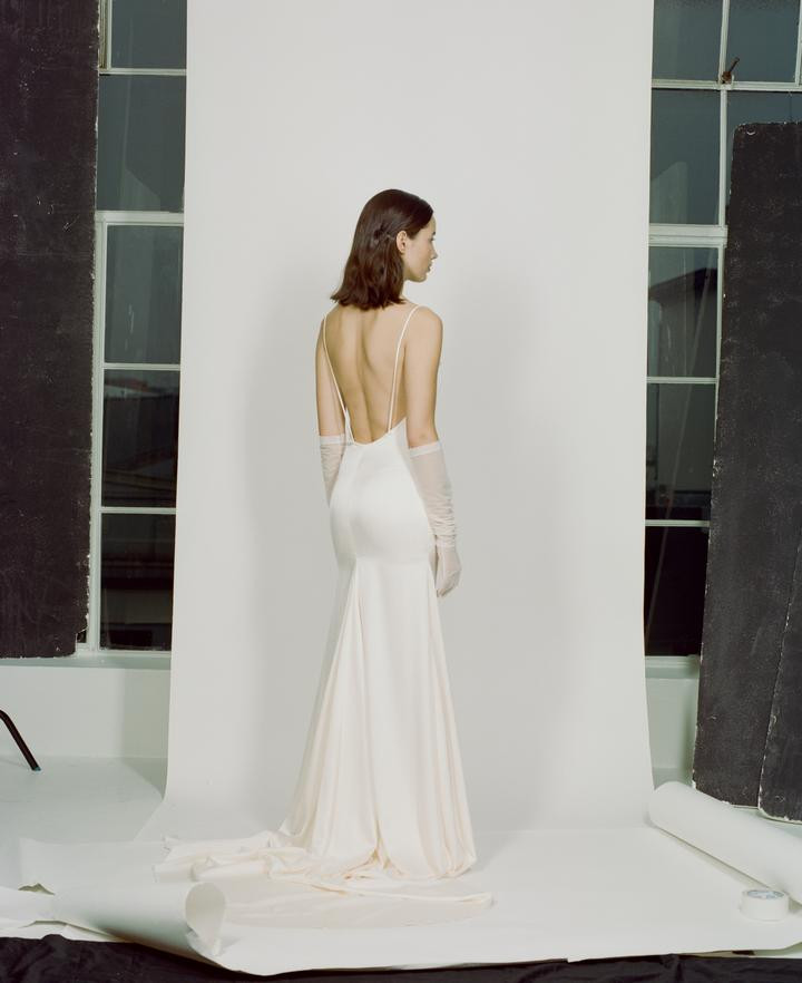 Bride wearing white silk wedding dress by Paris Georgia's new collection with sheer, long gloves.