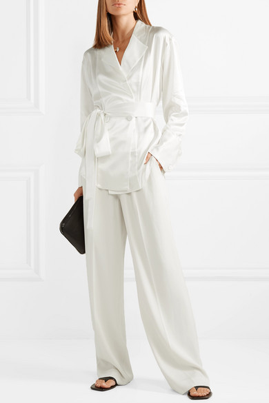 Bride wears white, 100% silk sating bridal blazer and straight leg pants with a pearl necklace, earrings and flats.