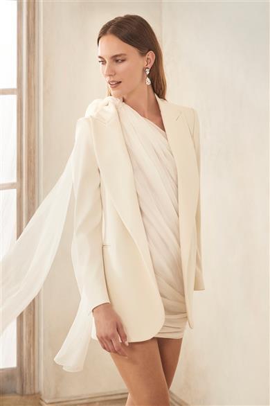 Bride wears Oscar de la Renta Bridal Fall 2020 white, short wedding dress with blazer.