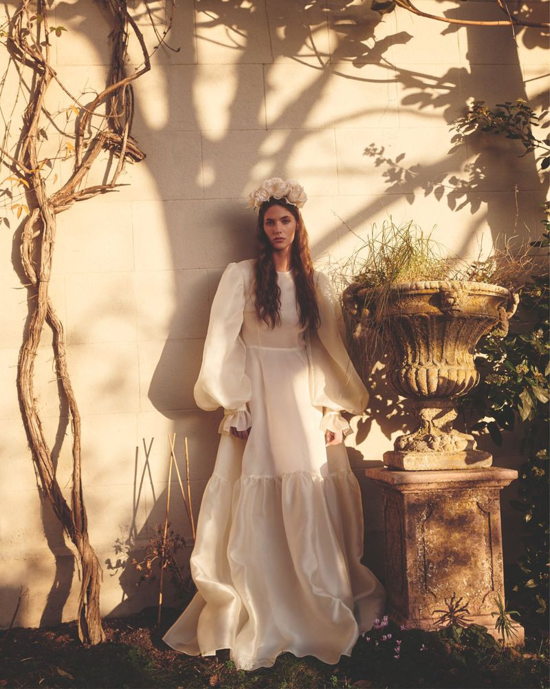 Model wearing long sleeve billowy wedding dress from Matches Fashion Wedding Edit.