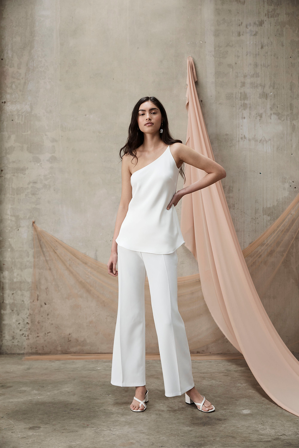 Bride wears white bridal pants and a white silk camisole top by Prea James Bridal, with minimalist sandals and pearl earrings.