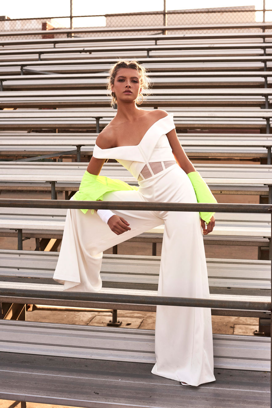 Bride wearing bridal off-the-shoulder jumpsuit with cutouts and boning as well as wide leg pants with hair loosely tied back.