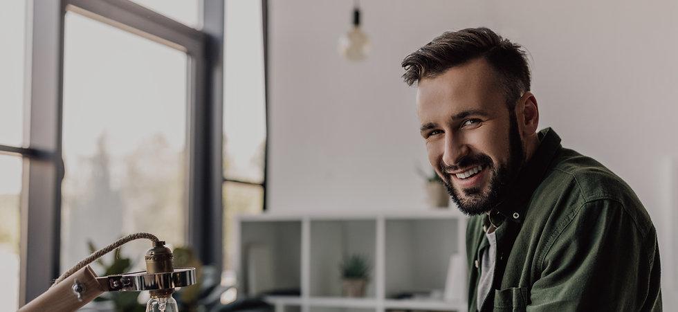 bearded-businessman-in-casual-clothing-smiling-at--NVFMJUV 1.jpg