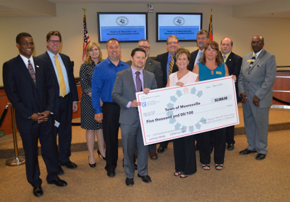 Realtors® Matt Reyes, Todd Long, Alison Royal-Combs and Sonya Leonard present a check from the Charlotte Regional REALTOR® Association to Mooresville Mayor Miles Atkins and the Town Board of Commissioners