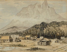 Collection of low log buildings in an open field with A large mountain [Castle Mountain] rising up in the distance. Mountain appears hazy, almost unfinished.