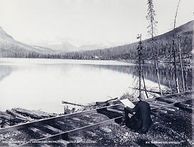 Mountain landscape with large lake dominating the centre. A small white building and storage tank [possibly a refueling station] can be seen on the far side of the lake. Train tracks run the width of foreground and seated figure [known to be Fredrick M. Bell-Smith] at easel in bottom right corner.   Title typed in bottom left corner. Manufacturer�s mark �WM. NOTMAN & SON, MONTREAL� typed in bottom right.