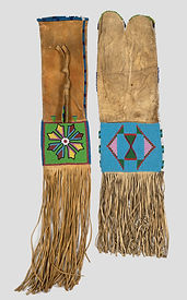 A long rectangular leather beaded bag. 37 cm fringe below a flower design with green background. Top edge is boarded with dark and light blue beads.