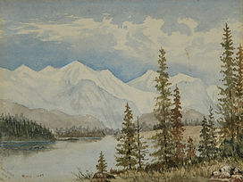 Large river [The Bow River] with snow-capped mountains at back and stands of conifers on the banks. River winds from left foreground into right background. Stand of trees at right foreground.