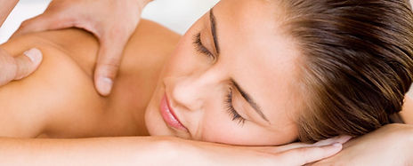 Woman is laying on her face on her hands as a massage therapist works on her shoulders.