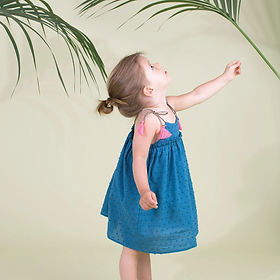 Girl weaing Children's Designer Clothing Brand Airfish's Leon Dress in peach color