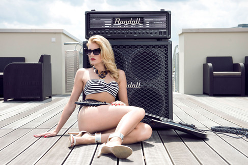 Girl in bikini leaning against a commercial randall amp