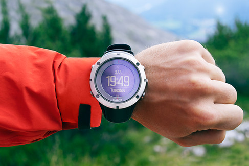 Hand with outdoor gear, wearing a Suunto watch, in front of mountains