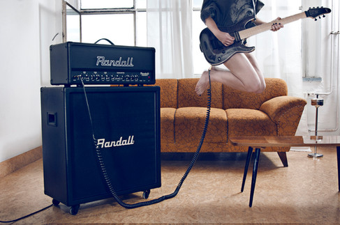 Randall guitar amp advertised with girl jumping playing guitar in her living room