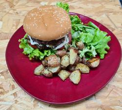 Burger maison accompagné de pommes de terre au four et légumes frais