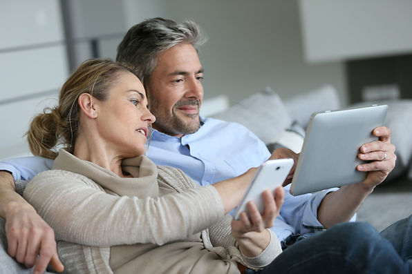 Mature couple at home using smartphone a