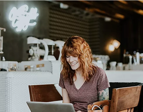 A woman looking happily working on a laptop