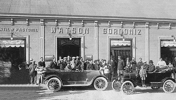 fotografia antigua de la fachada de un local comercial. se ven varias personas posando y 2 autos antiguos.