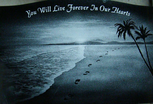 """Hand-etched scene of Hawaii """"Footsteps In The Sand"""". Black granite"""