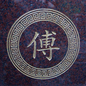 Chinese surname with Greek key frame on red granite