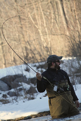 Fly fisherman hooks a big fish on the LIttle Juniata River in central Pennsylvania.