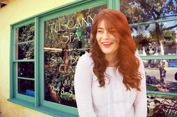 smiling woman in front of tuscany spa window