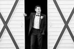 Groom posing by the barn door.