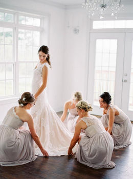 Bridesmaids adjusting the bridal gown