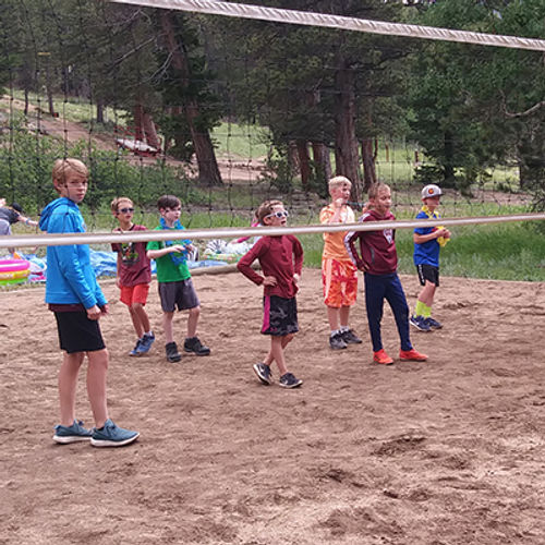 seven youth on a sand volleyball court, waiting for the ball to come their way