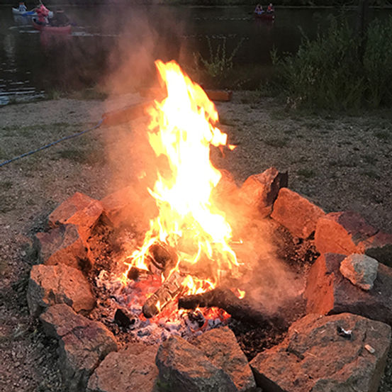hotdog being roasted over campfire in stone fire ring