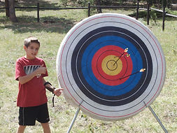 boy gives two thumbs up standing by his archery bullseye and two near bullseyes