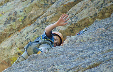 boy in climbing gear waves from his place on a rock wall