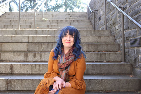 An image of Jessi Huffman, Licensed Professional Counselor. She has blue hair, an orange wrap, a brightly colored scarf, and is looking kindly at the camera.