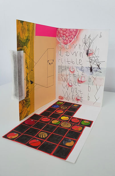 "A 3D standing collage including beige-gold area, bright pink strip, a section of an old floral print, child-like handwriting reading ""down, little, what, by"", prints from pomegranate seeds, a geometric fine-lined black shape at the letters CERES, along with a ground area with plack squares and circular bead-like paintings."
