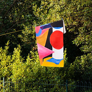A very bright abstract painting is hanging over a suspended line, outside, with trees visible in the background. The painting is red, pink, orange, blue, black and white.