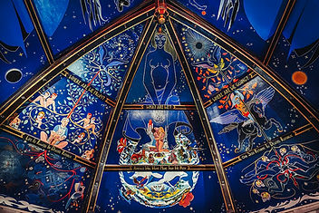 Alasdair Gray's celing mural in  Òran Mór , Glasgow. CC image. The mural is highly detailed and depicts several narrative illustrations that range from mythical symbolism, astrology and the relationship between human life and 'nature'. The background colours are strong blues and the images are bright white outlines with other vivid colours.