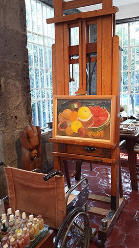 A colour photograph of the interior of Kahlo's Casa Azul, or Blue House. In shot is a wooden easel with painting of friut and a wheelchair facing the easel; windows with small panes are visible and tiny glass jars in the foreground.