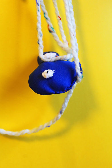 Aimee Haldane, 'Experiment for Phantasos' 2020, Dream catcher mixed media installation at Studio Pavilion, Glasgow. Bright yellow background with sculptural elements hanging ade from blue fabric and white wool or string.