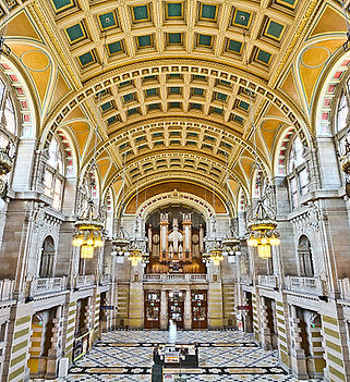 Photograph of the interior of Kelvingrove Museum and Gallery's Centrall Hall. The organ can be seen at the far end of the room, the panelled ceiling is golden and the arches balconies and walls are white.