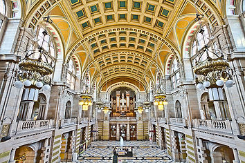 Image: Kelvingrove Museum and Gallery Central Hall by Michael D Beckwith  (CC use). A colour photograph of the interior of the main hall; the spce is very bright with pale tiles and stonework and a golden arched ceiling. There's a first floor level that overlooks the hall down the left and right sides. At the far end is a large pipe organ dominating the first floor balcony area. Grand gold and white glass lights hang througout the space.