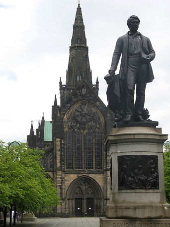 Glasgow cathedral in the backgound with the David Livingstone statue in the foreground: very dark in colour, a man stands holding a book (a bible).
